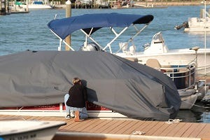 person-putting-on-pontoon-boat-cover
